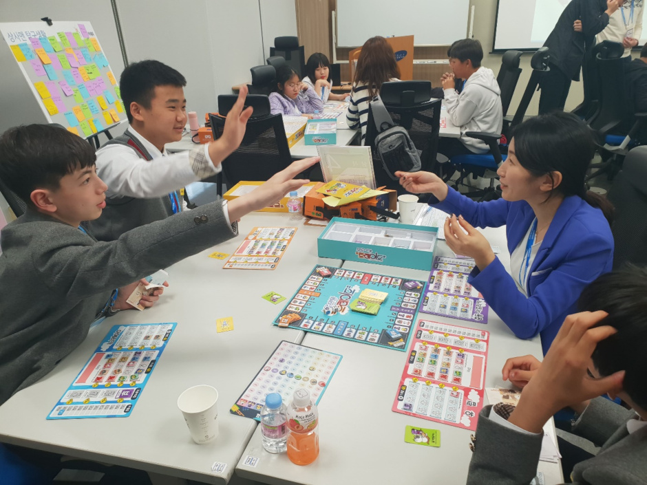 Students from Paju Kwangil Middle School and Bucheon Naedong Middle School play the Monopoly-based trading game Blue Marble with a Samsung C&T employee at the Trading & Investment offices of Samsung C&T.